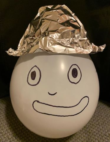 photo of balloon head wearing a foil hat